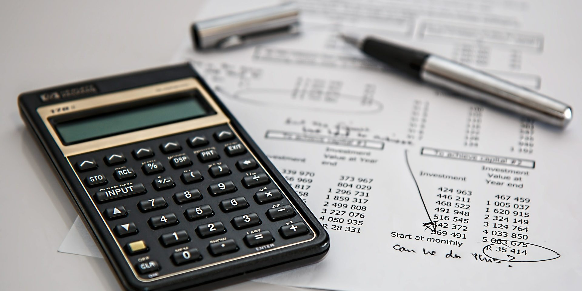 Das Foto zeigt einen Taschenrechner als Kakulator und einen Stift und ein Blatt Papier.