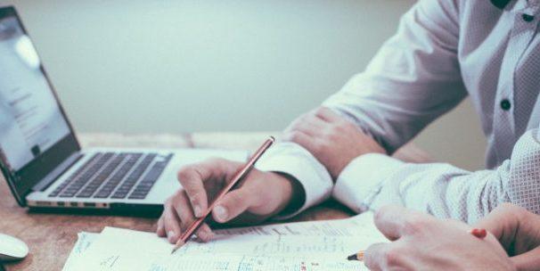 Auf dem Foto sieht man 2 Personen, die Online und Offline mit Stift und Papier und Laptops arbeiten.