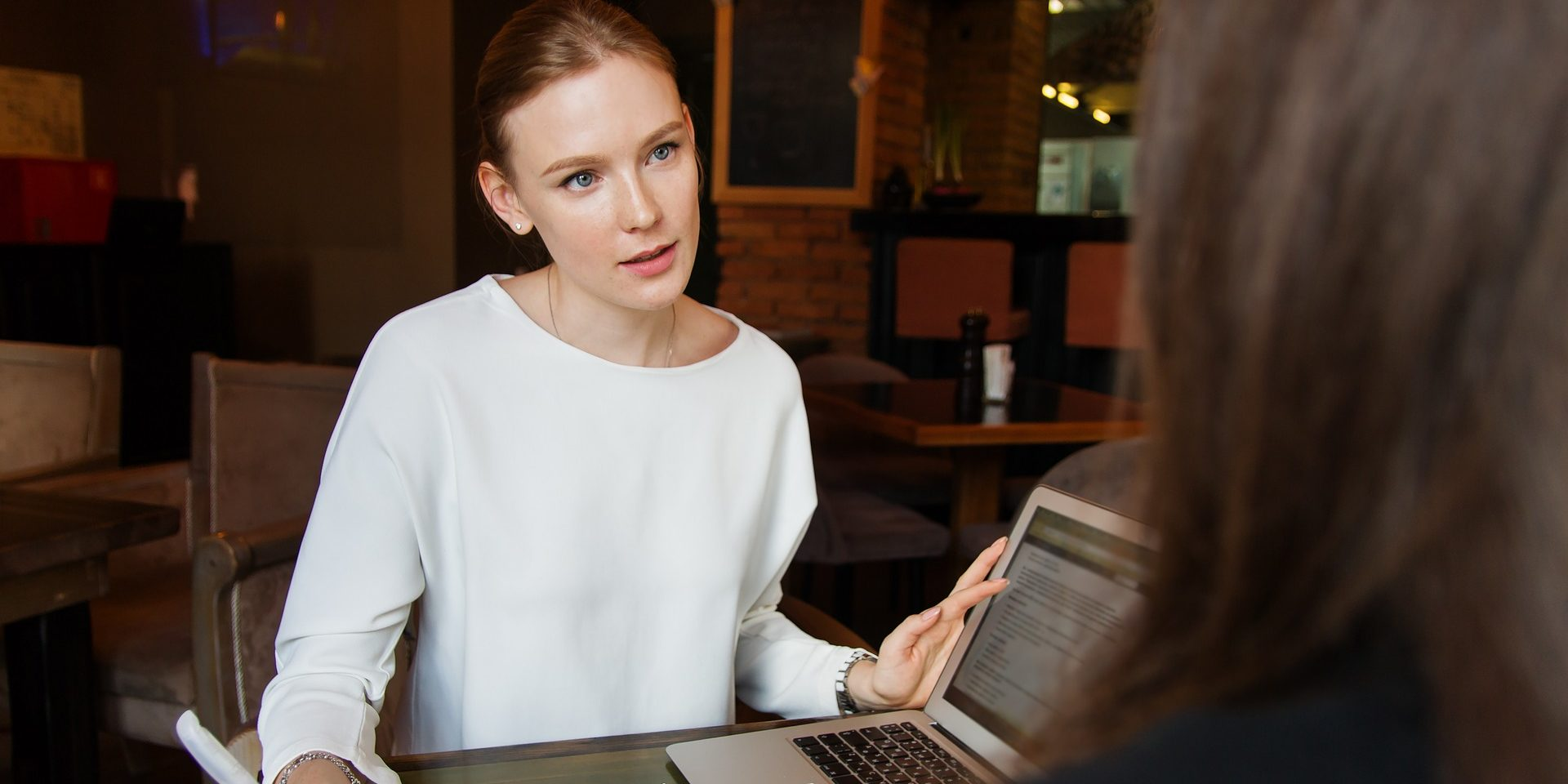 Das Foto zeigt eine Businessfrau mit Laptop und Notizen im Gespräch mit einer weiteren nicht eindeutig erkennbaren Person.